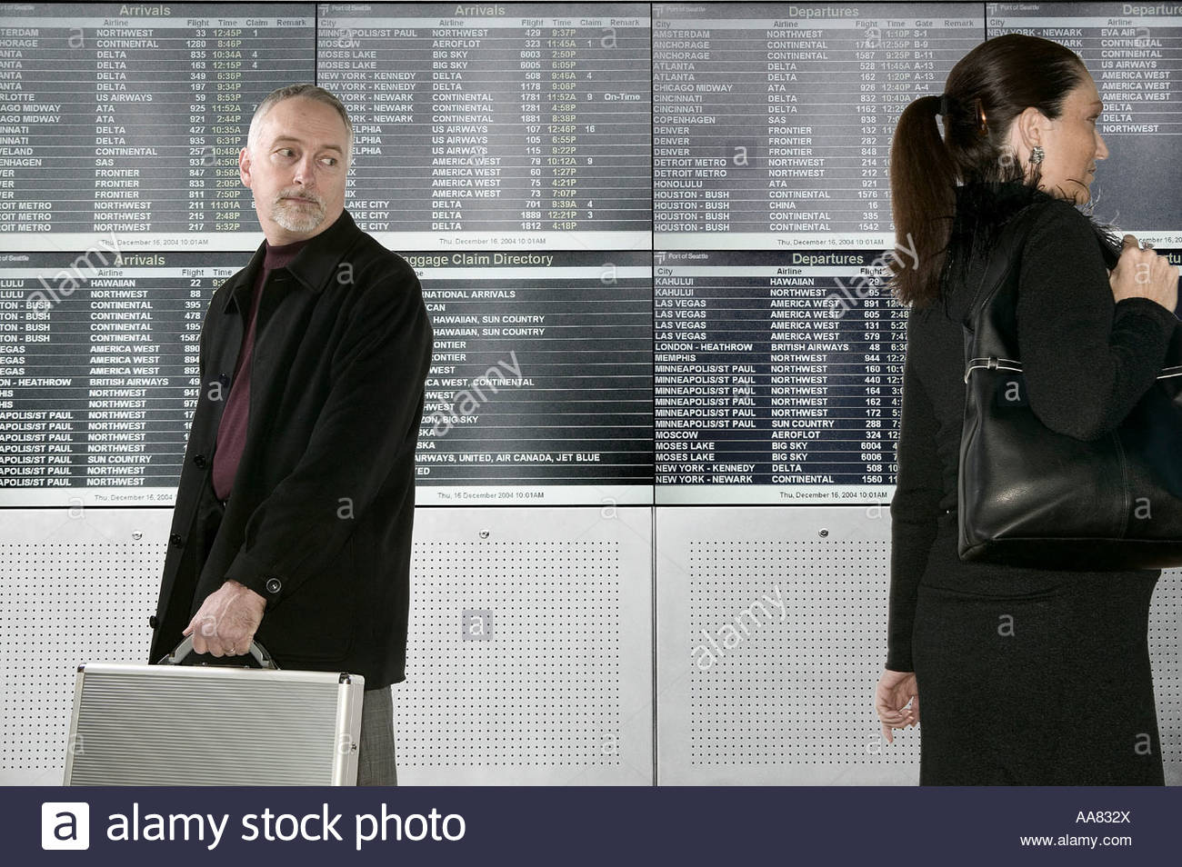 Man looking at younger woman in airport - Stock Image