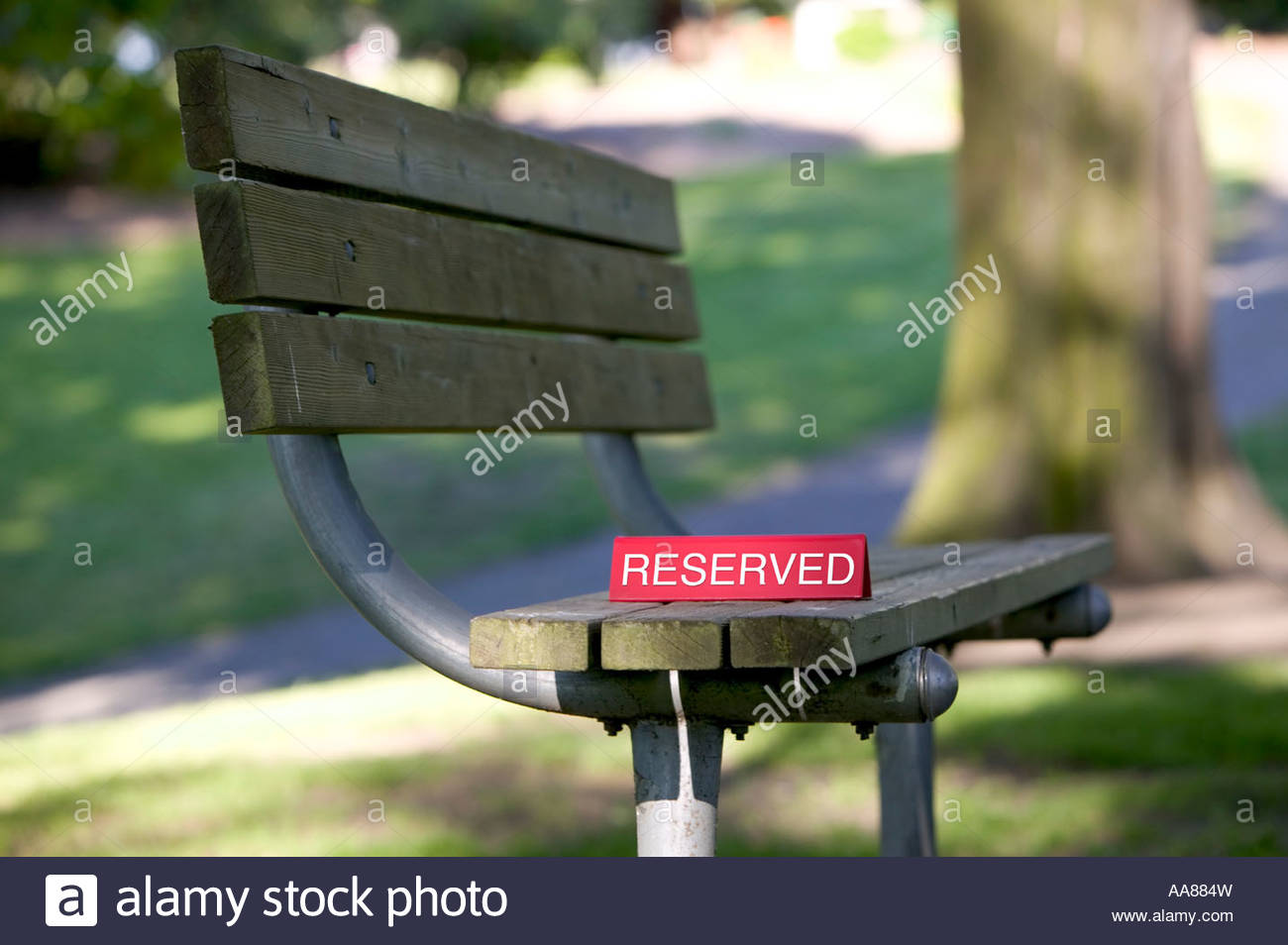 Park bench with reserved sign - Stock Image