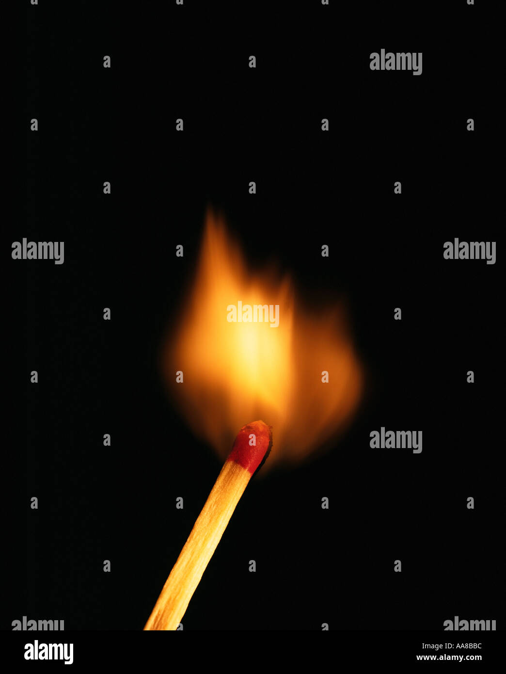 SINGLE BURNING MATCH ON BLACK BACKGROUND - Stock Image