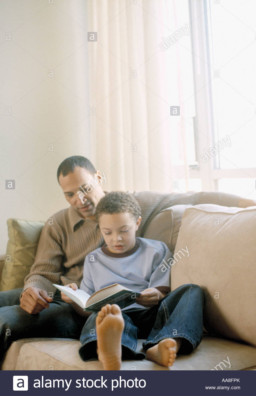 African father and son reading on sofa - Stock Image