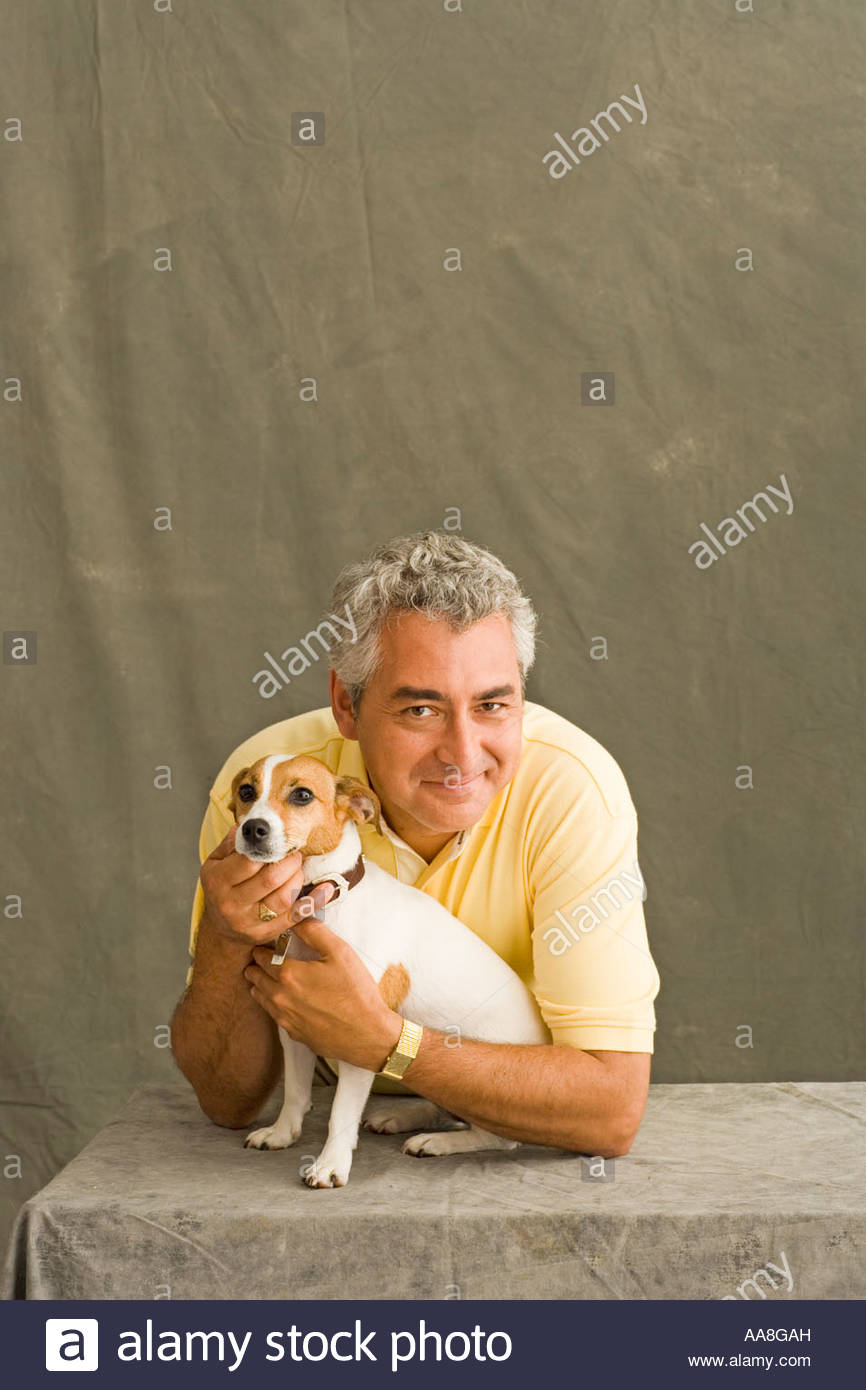 Middle-aged man hugging small dog - Stock Image