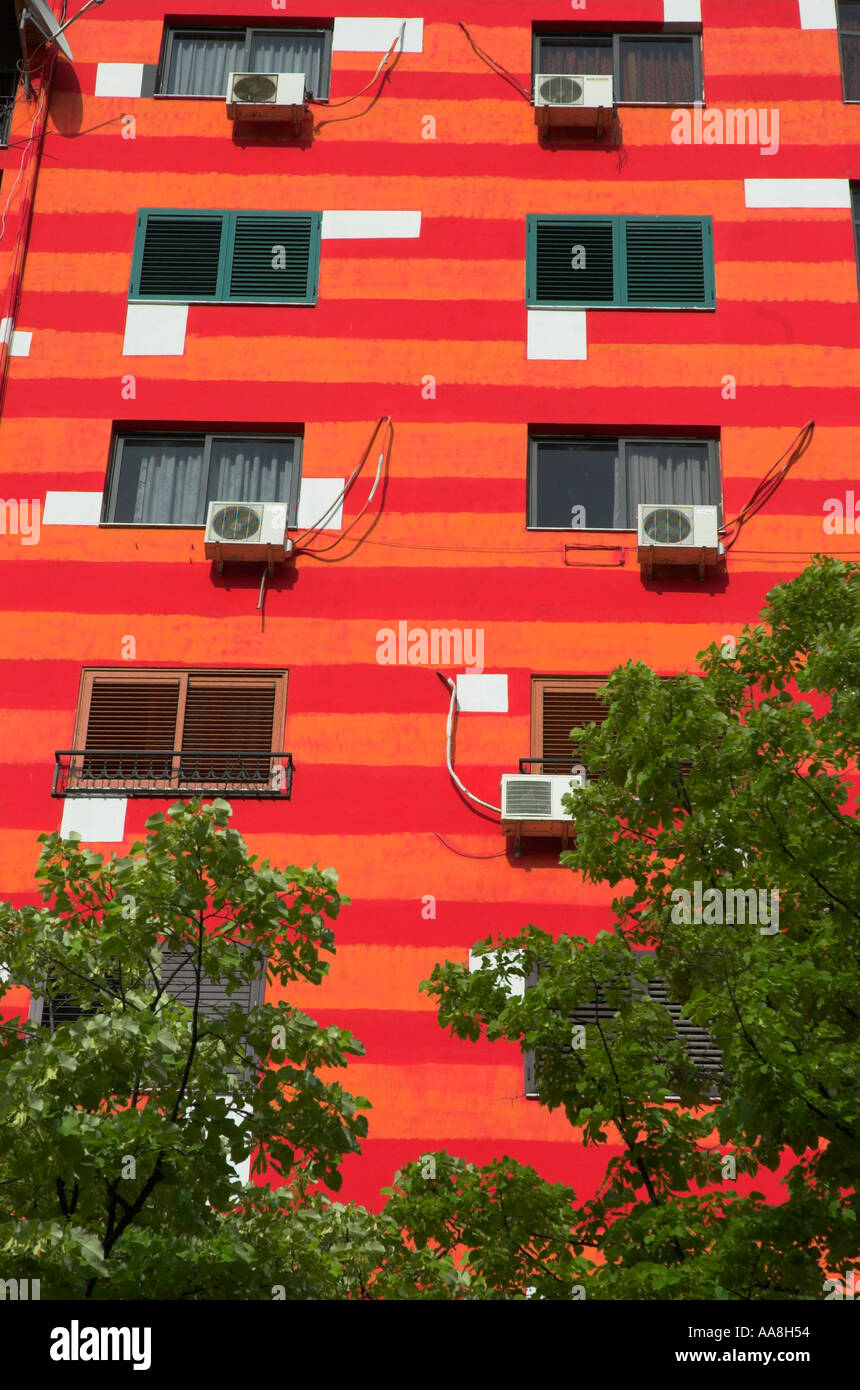 Albania Tirana Downtown Blloku close up of repainted housing buildings in bright red and orange paint vertical - Stock Image