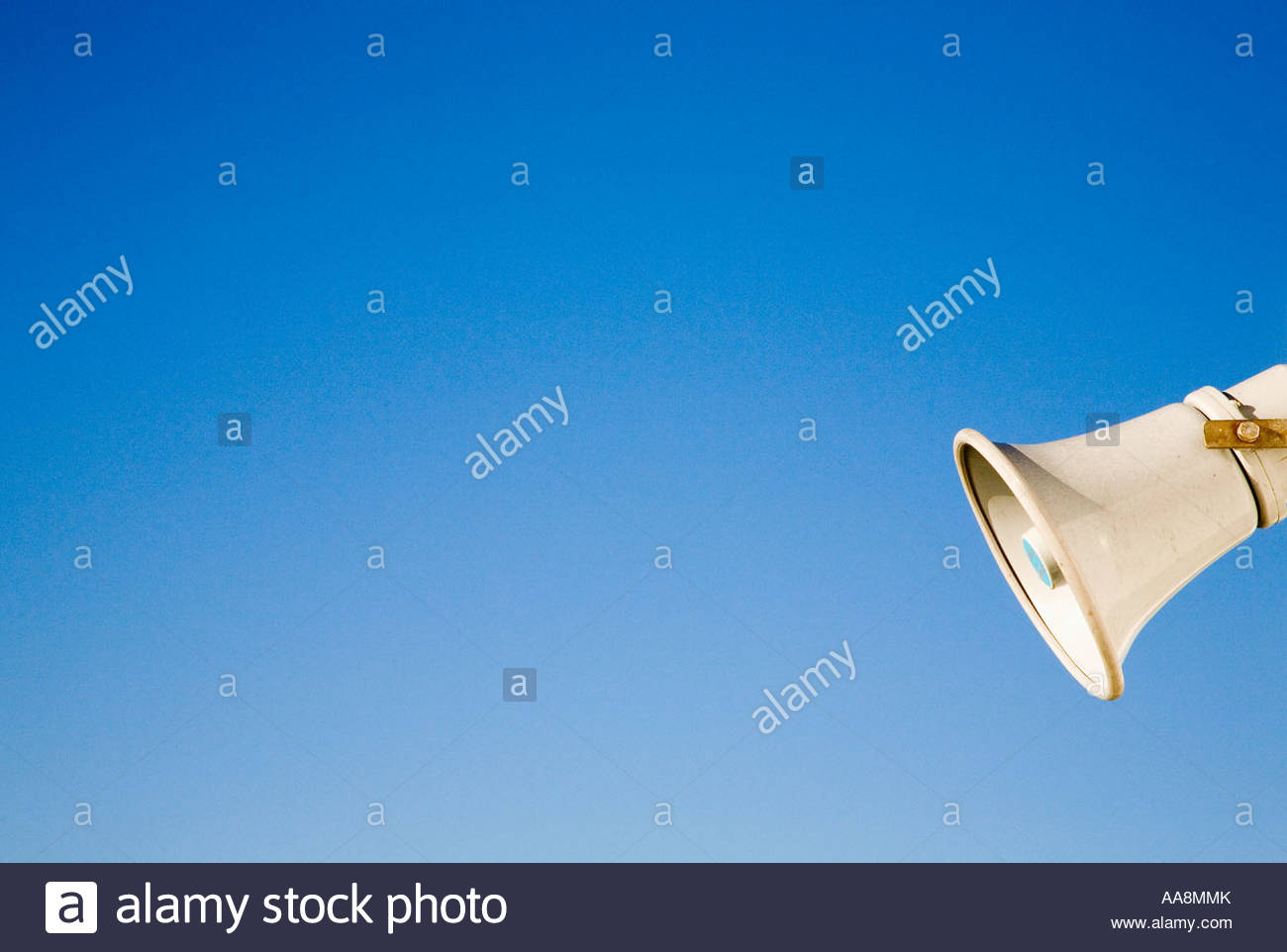 Off-centered view of megaphone on blue background - Stock Image