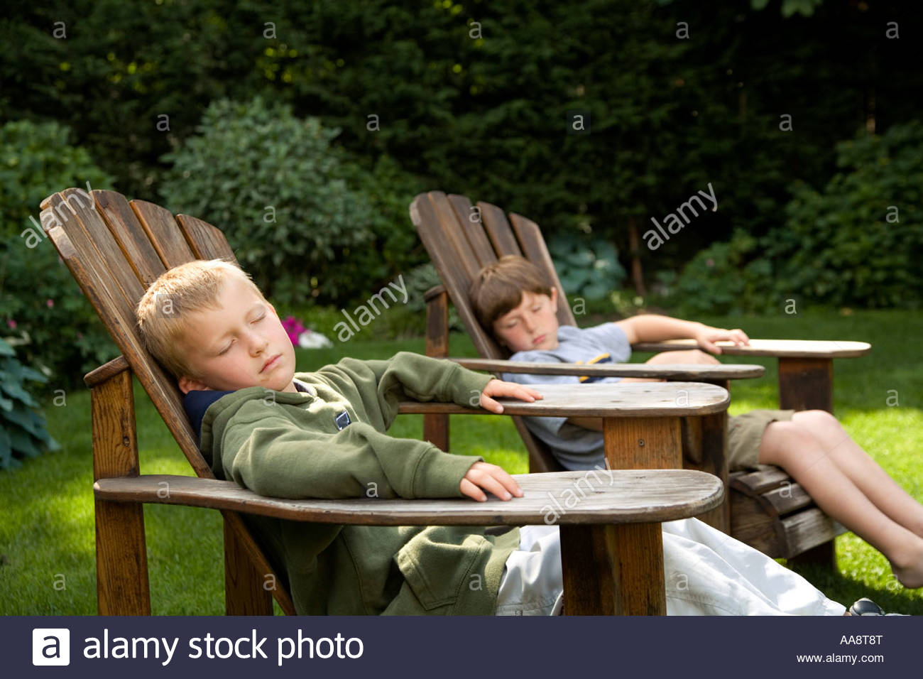 Young Boys Relaxing In Backyard Lawn Chairs Stock Photo
