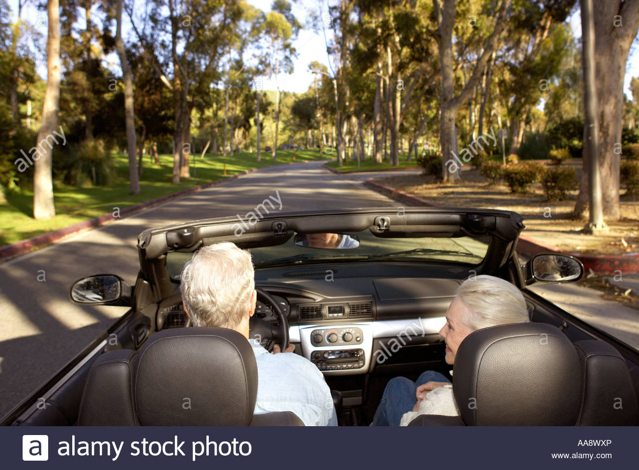 Senior couple driving in convertible - Stock Image