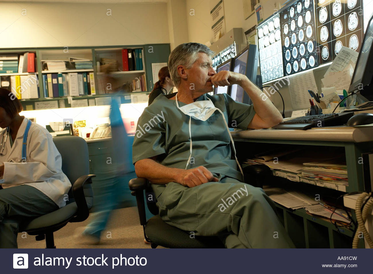 Male doctor looking at x-rays - Stock Image