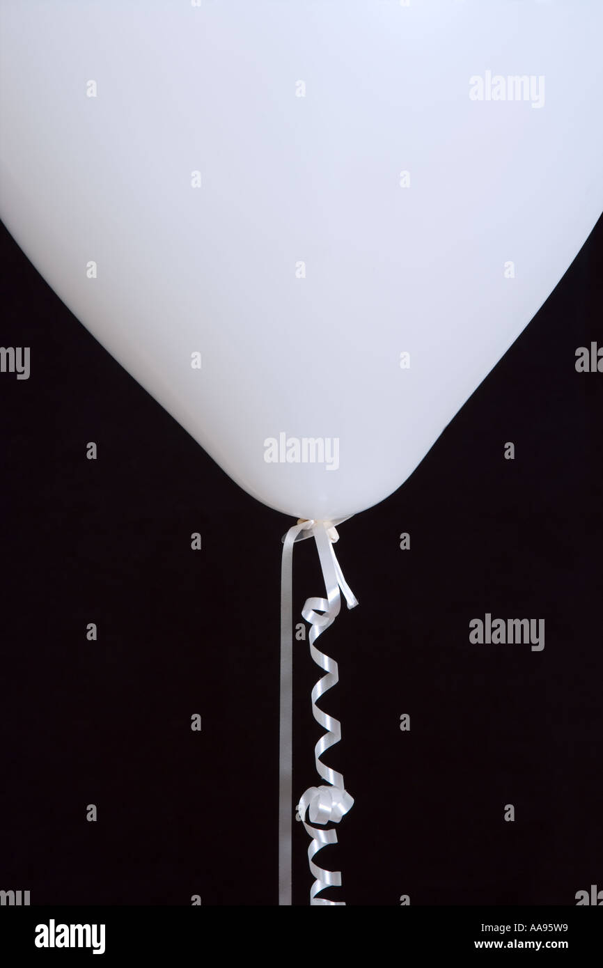 White balloon and curled ribbon against black background, close-up - Stock Image