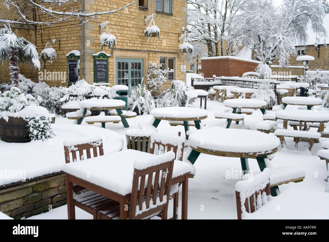 The chairs and tables in a pub garden covered by winter snow in the Cotswold village of Bourton on the Water Gloucestershire - Stock Image