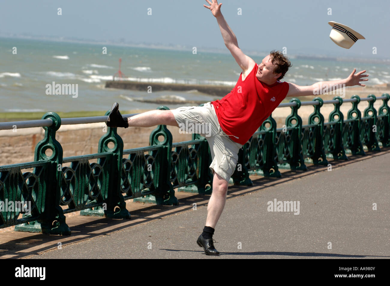 One overweight middle-aged man doing clumsy high kicking dance routine on Brighton seafront  as his hat blows off - Stock Image