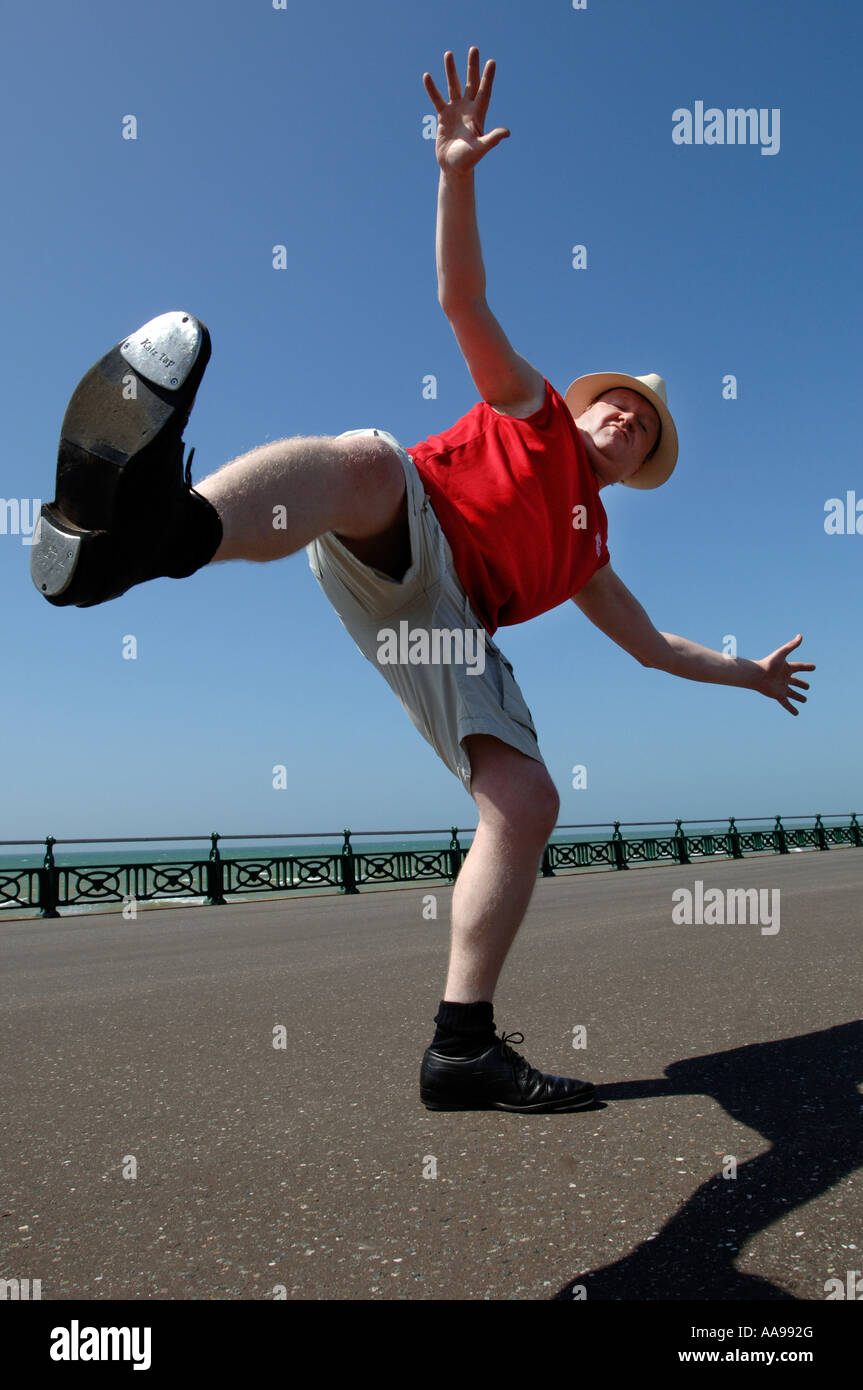 One Serious Looking Middle Aged Man Doing Clumsy High Kicking Dance Routine  On Brighton Seafront