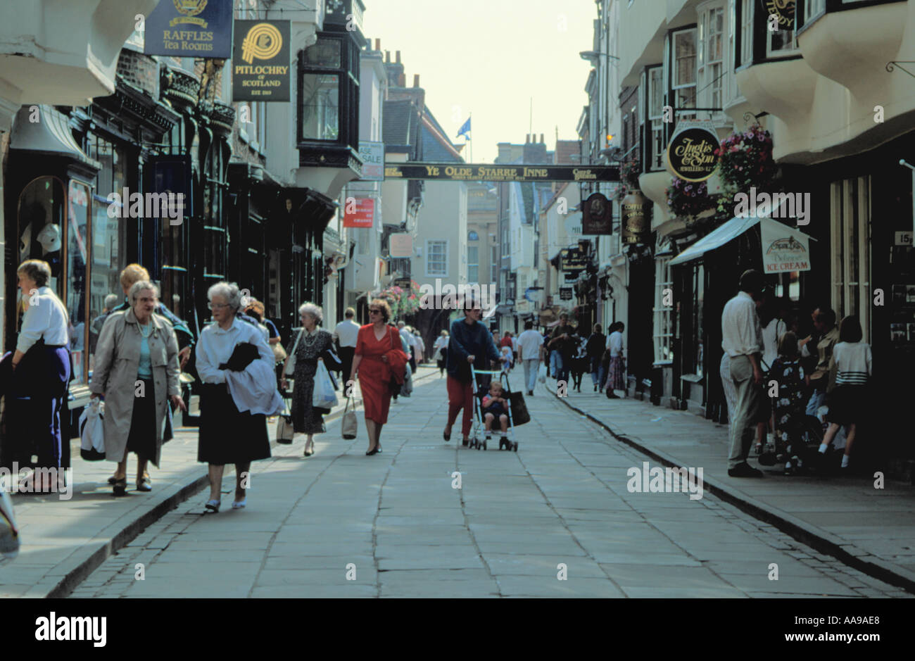 People walking on narrow pedestrianised picturesque Stonegate, City of York, North Yorkshire, England, UK. - Stock Image