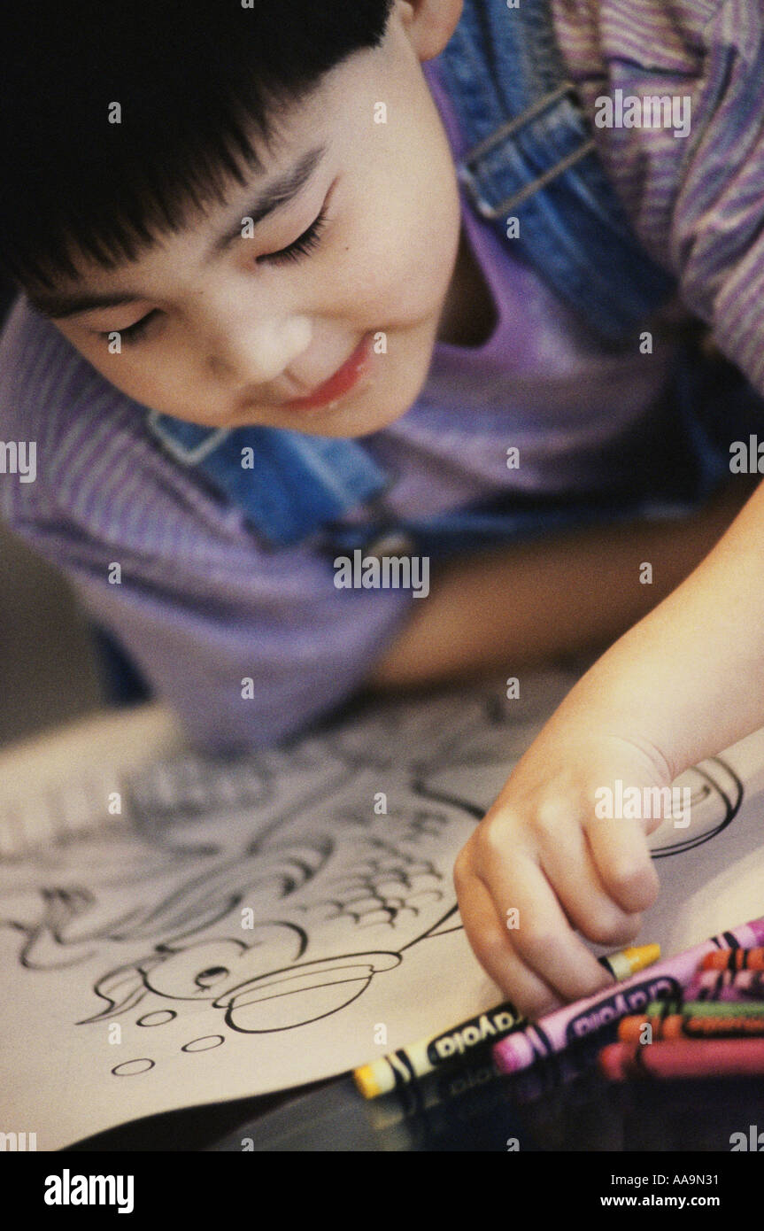 Boy Coloring With Crayons In A Book