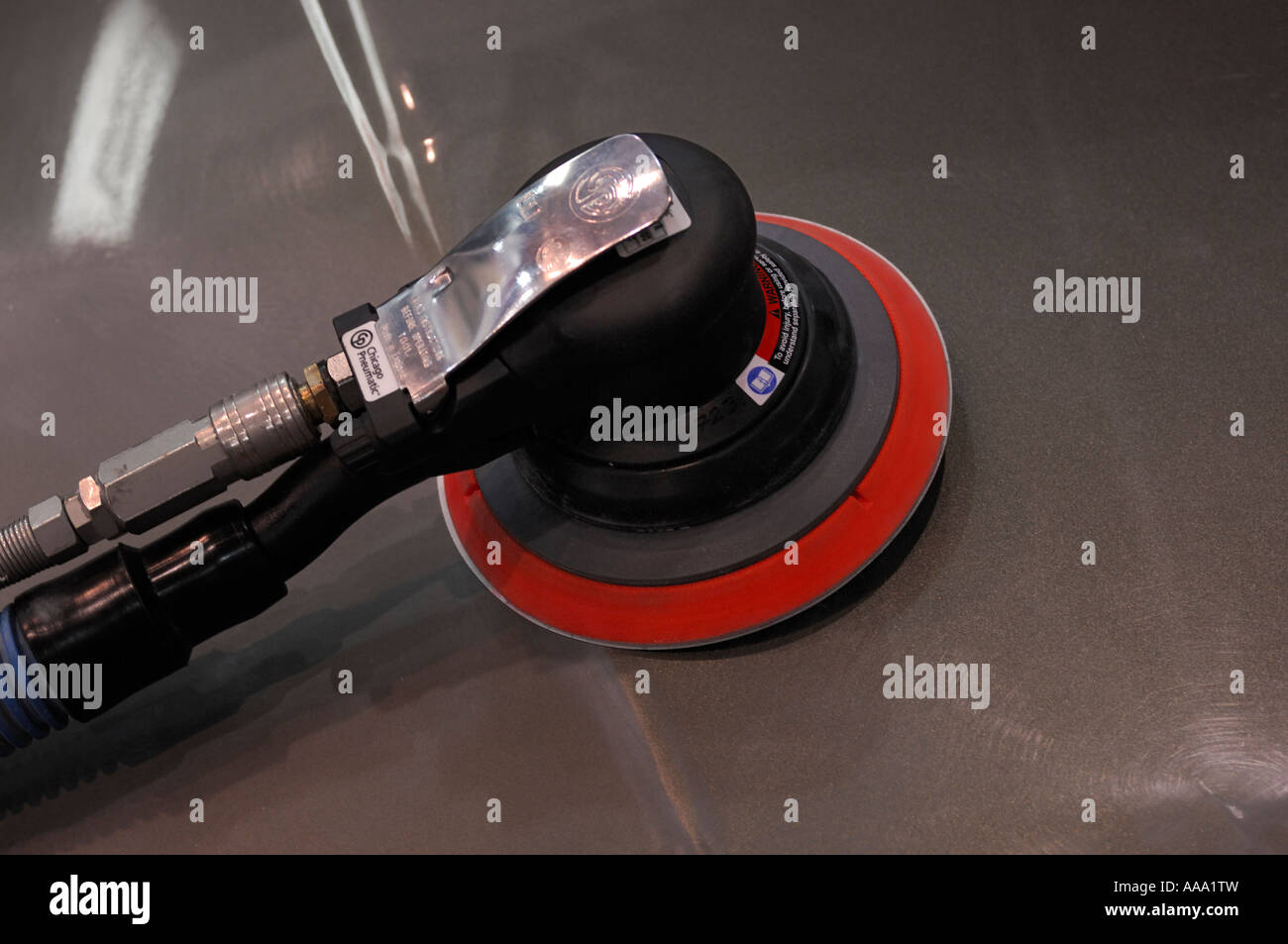 Pneumatic orbital palm air sander on a car hood Auto workshop repair shop tool - Stock Image