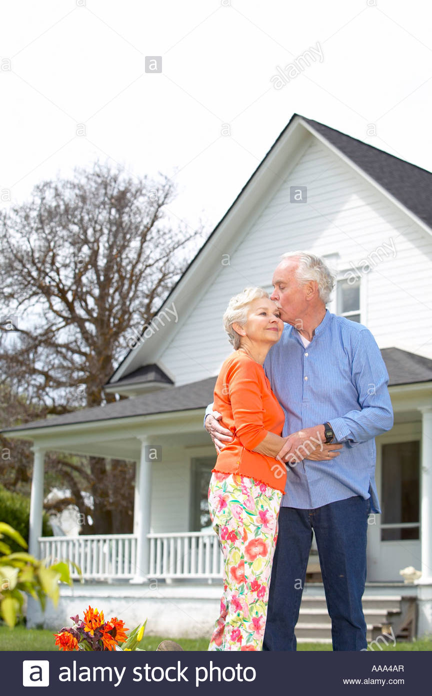 Senior couple embracing in front of house Stock Photo