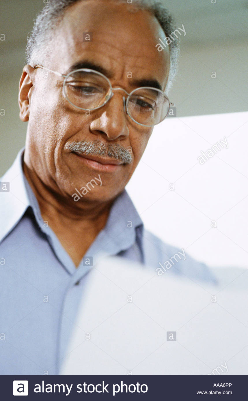African man examining piece of paper - Stock Image