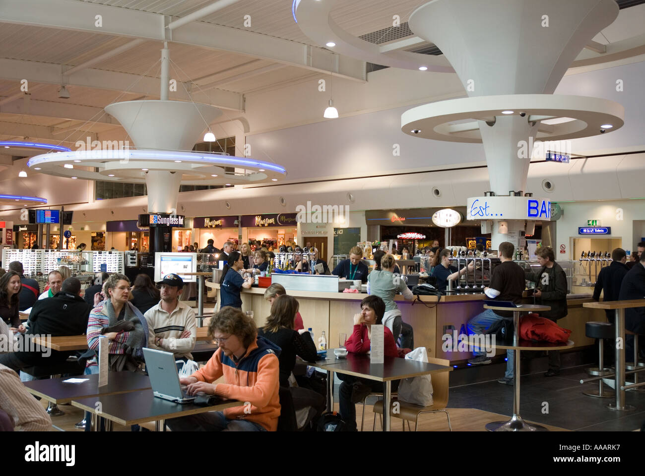 A man using his laptop computer at a bar and cafe at Luton Airport departure lounge - Stock Image