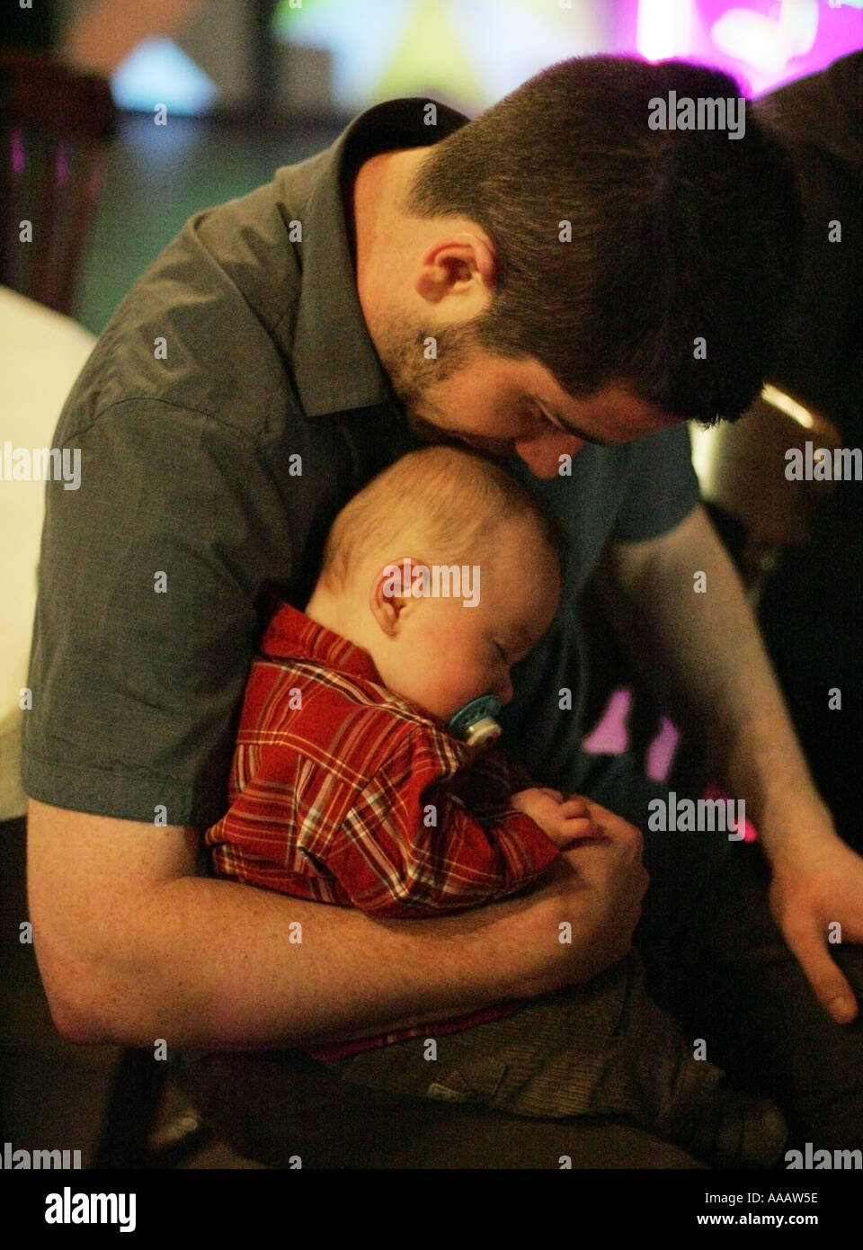 A sleeping baby held by the father - Stock Image
