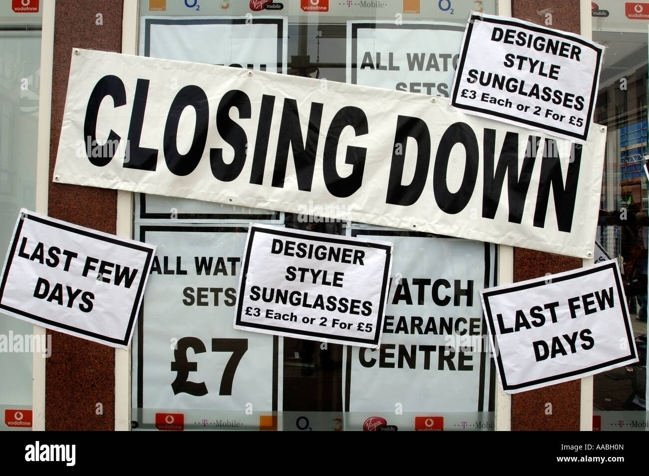 A shop window plastered with closing down signs - Stock Image