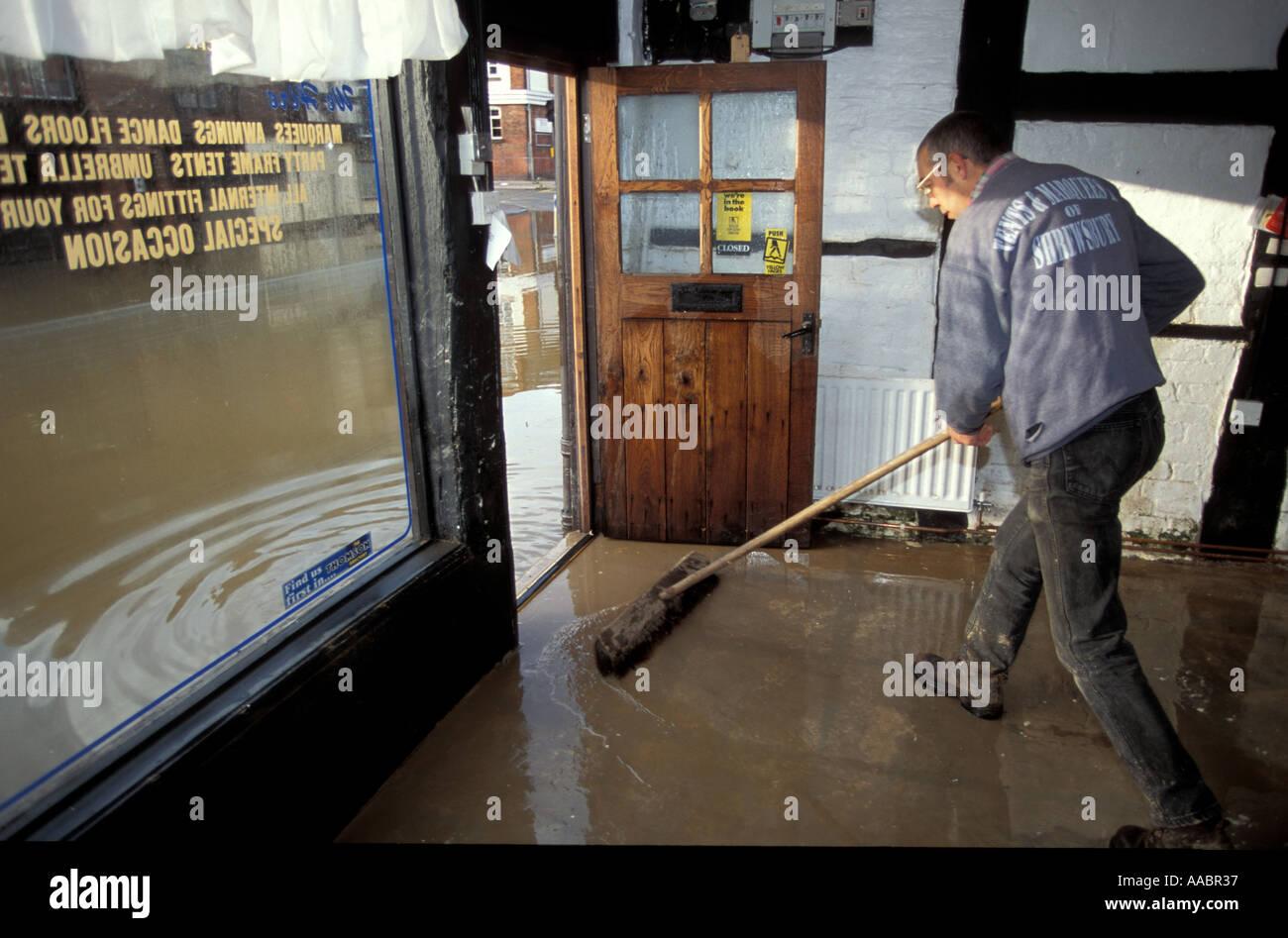 Cleaning up inside a flooded shop in shrewsbury Worcestershire England UK uk united kingdom great britain - Stock Image