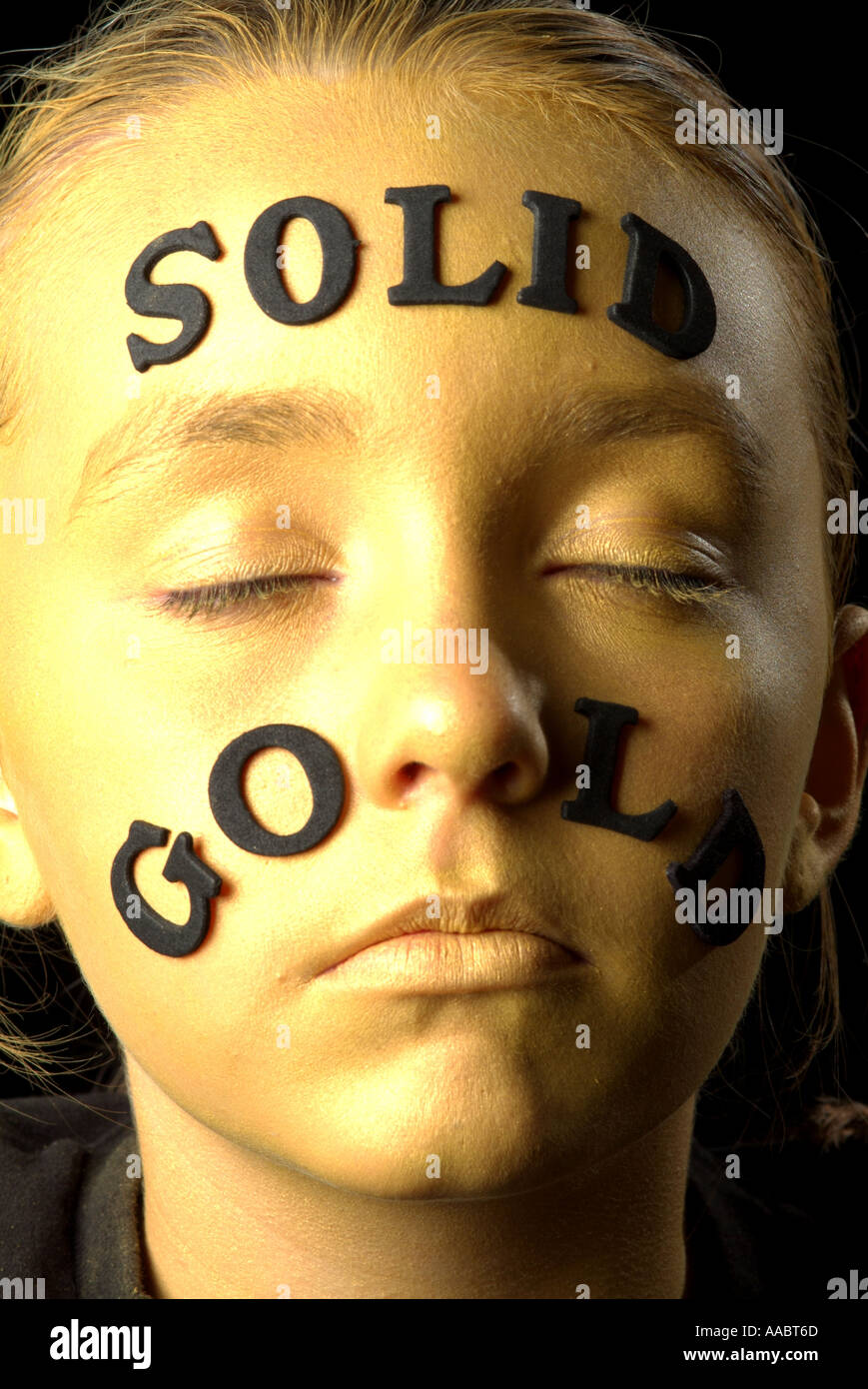 gold face girl with eyes closed faced solid gold lettering - Stock Image
