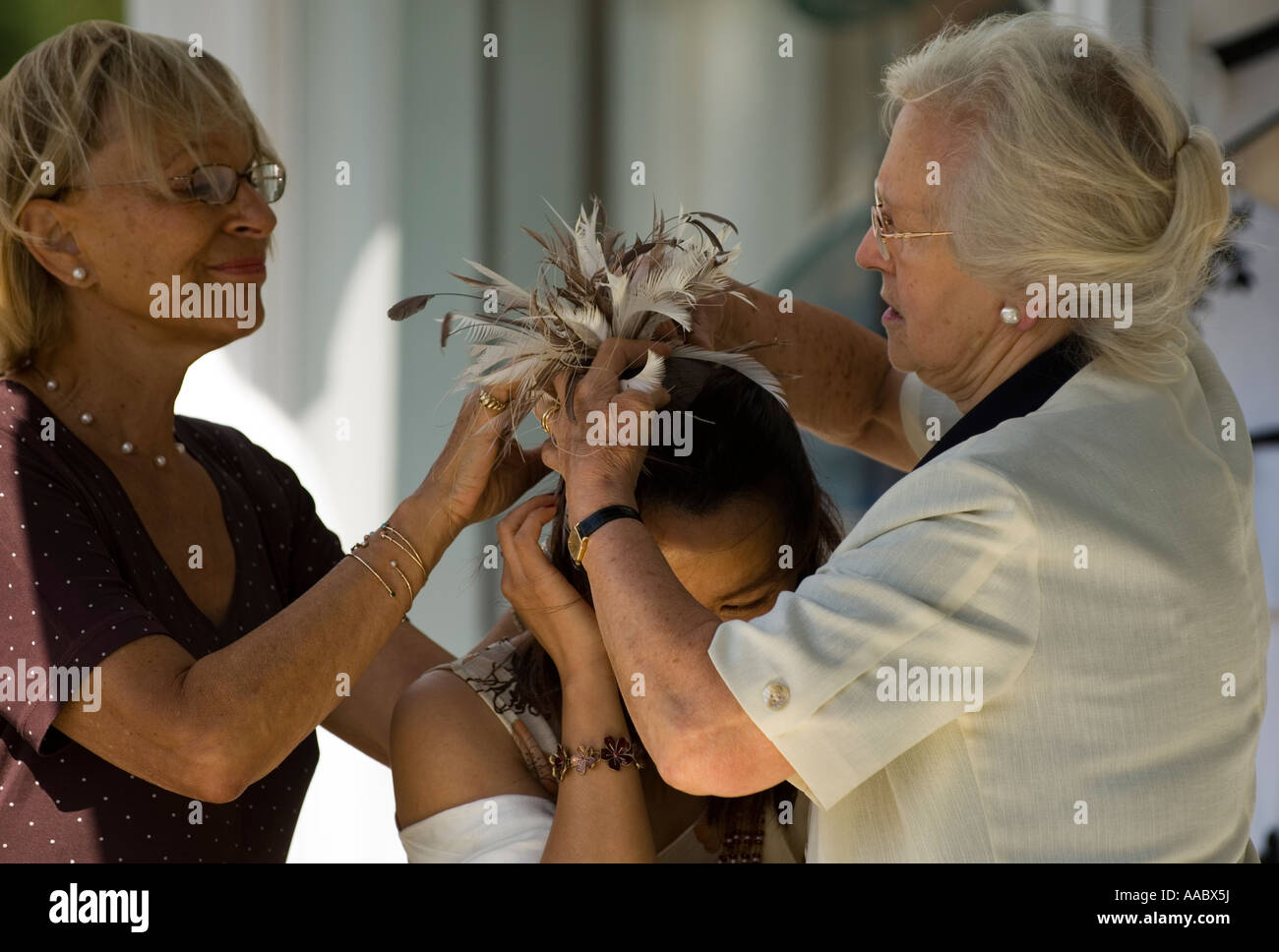 Milliners fitting a hat with pins during Royal Ascot - Stock Image