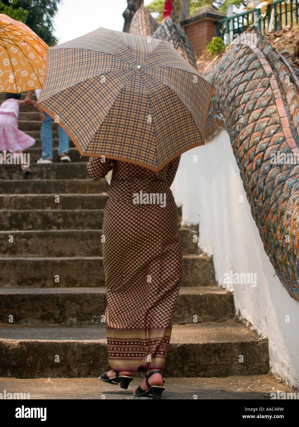 traditional Burmese dress woman climbing temple steps - Stock Image