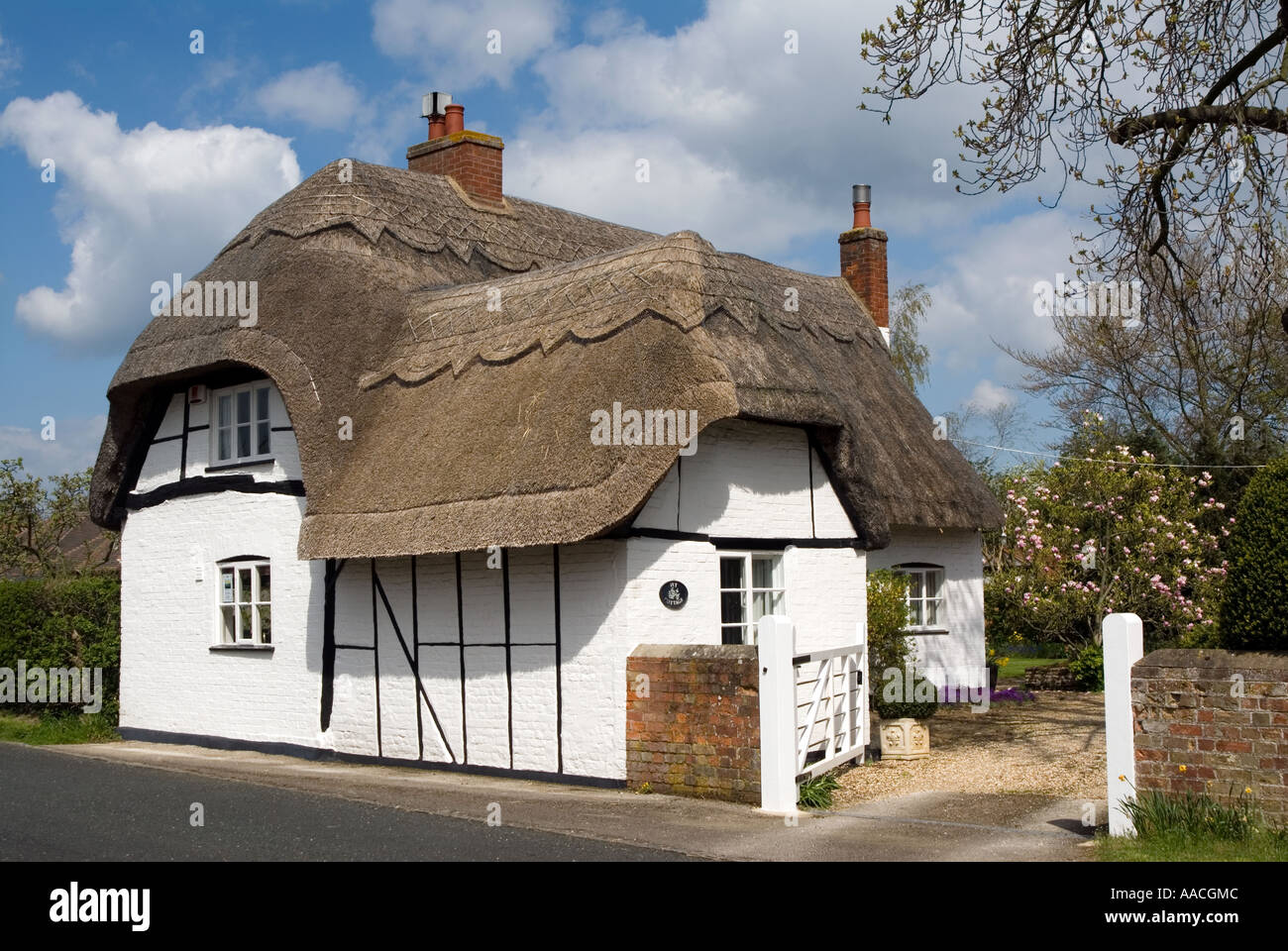 A typical traditional English country thatched house / cottage with white walls & black beams in Milton Keynes Village - Stock Image