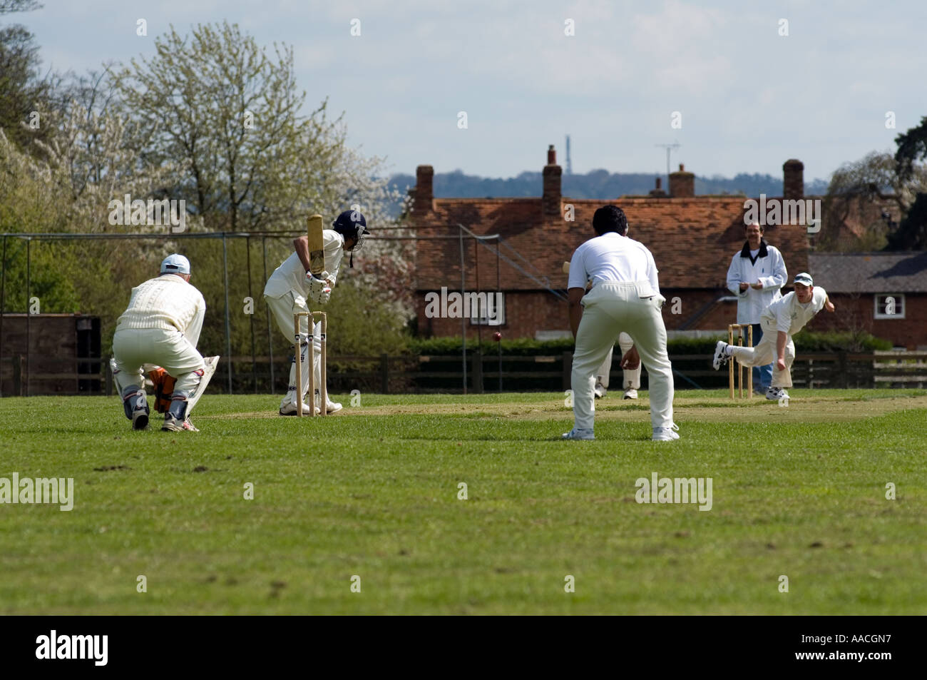 A traditional game of cricket in Milton Keynes Village - Stock Image