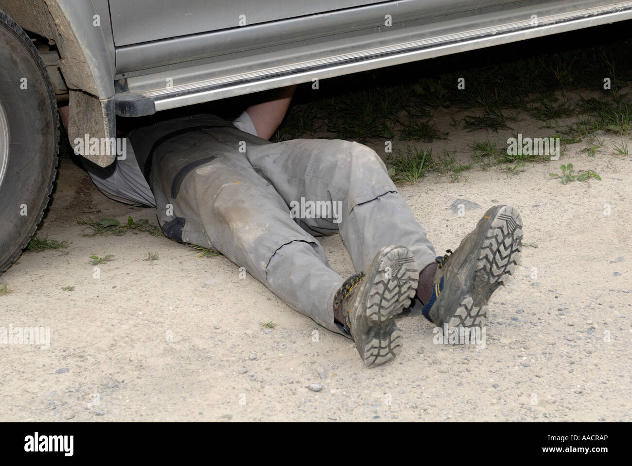 Man under a broke-down vehicle, Germany, Europe Stock Photo