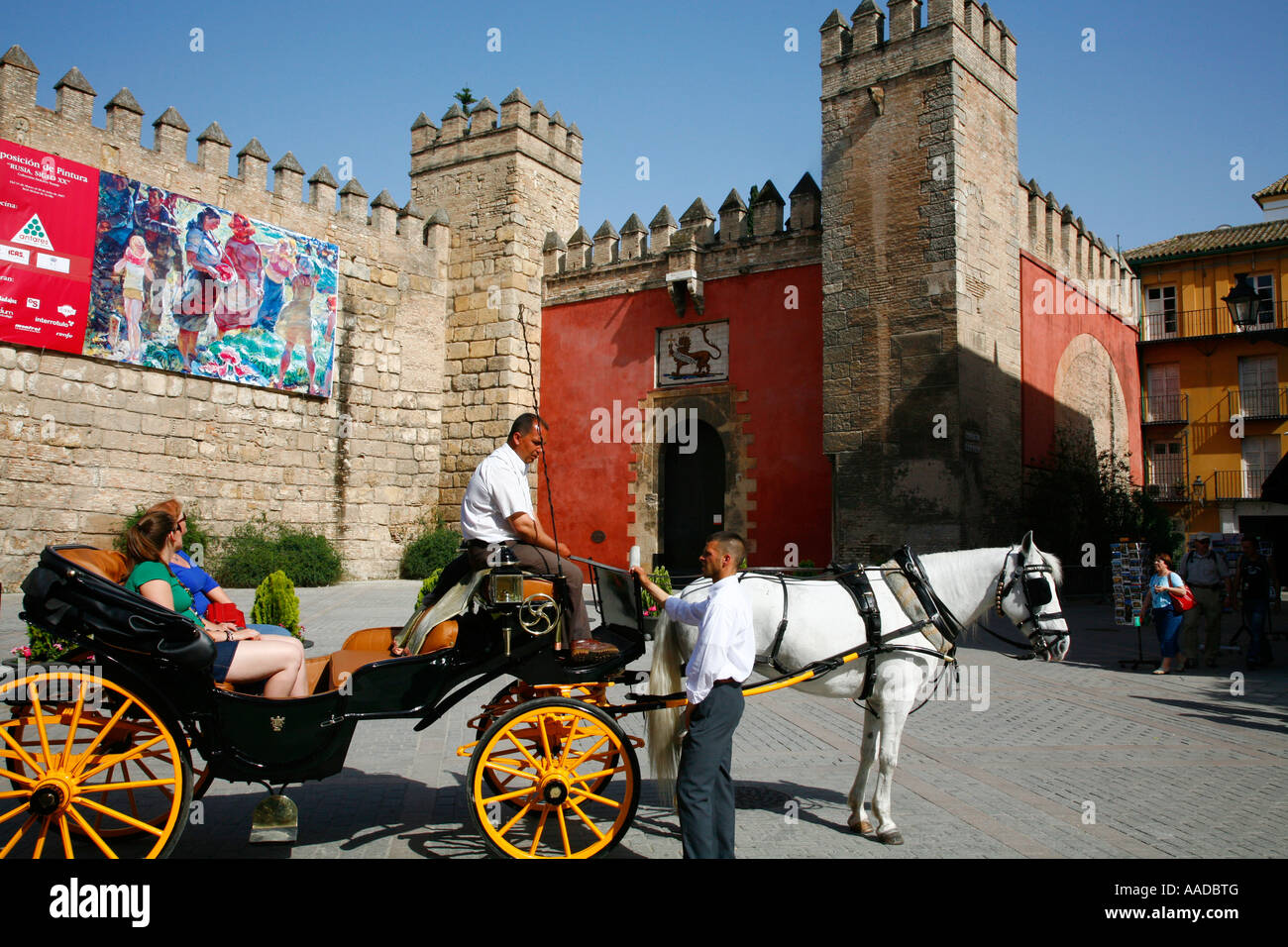 people sitting on a horse drawn carriage in front of the Alcazar Seville Spain - Stock Image