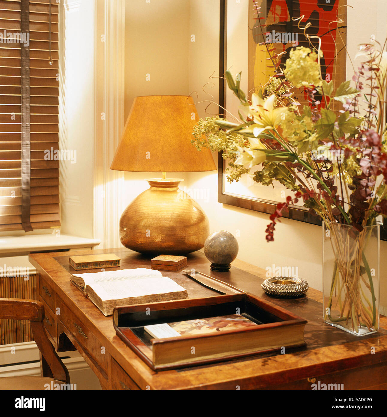 Gold lit lamp and flower arrangement on desk with open book - Stock Image