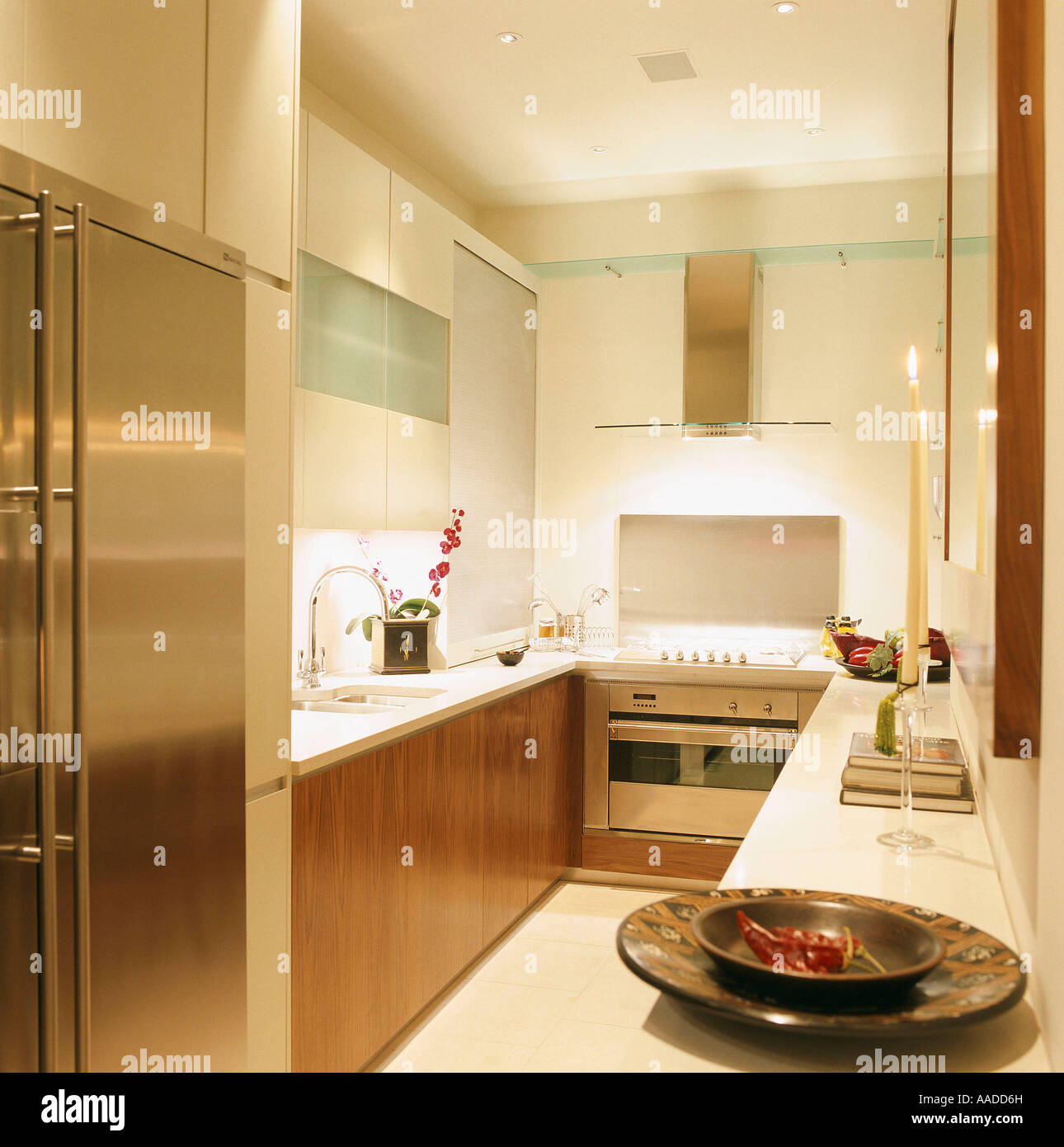 Galley kitchen with fitted wood units and stainless steel fridge - Stock Image