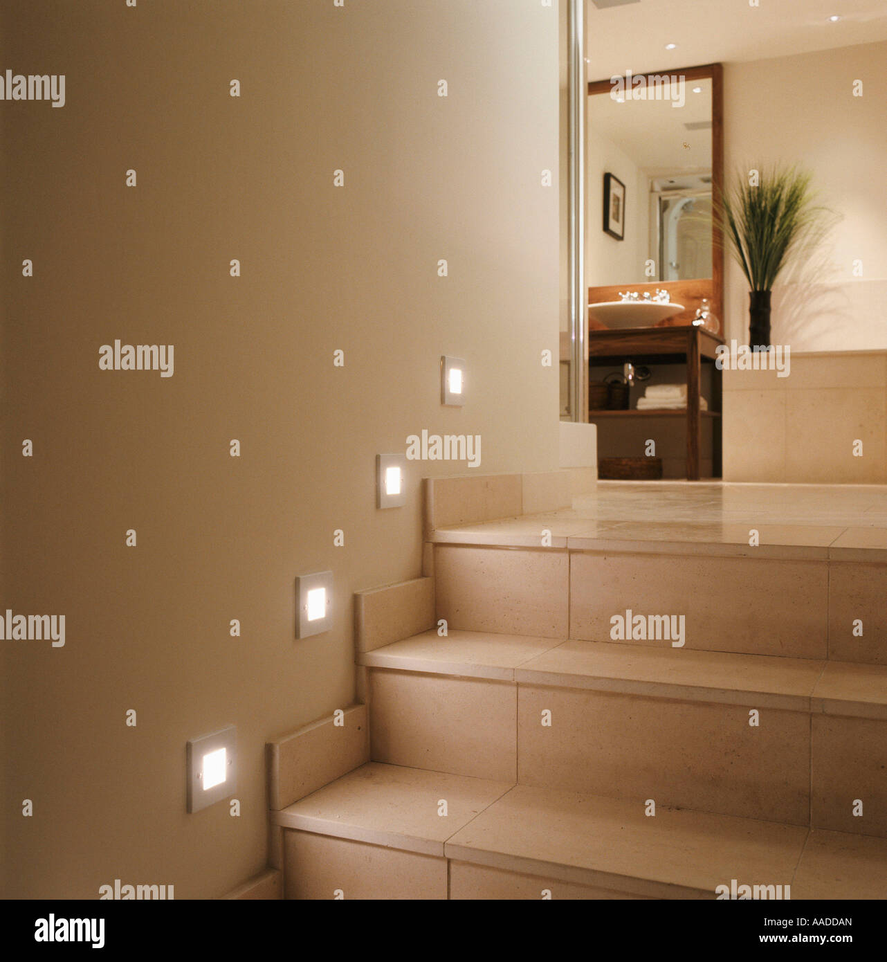 Spot lighting on tiled stairway to bathroom - Stock Image
