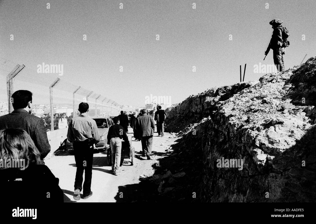 Palestinian crossing the lines in Kalandya checkpoint near Ramallah while Israeli soldier is on guard West bank Israel - Stock Image