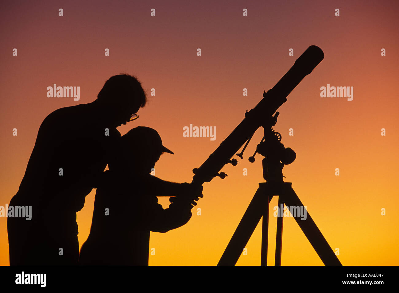 A father demonstrates to his child how to use a telescope - Stock Image