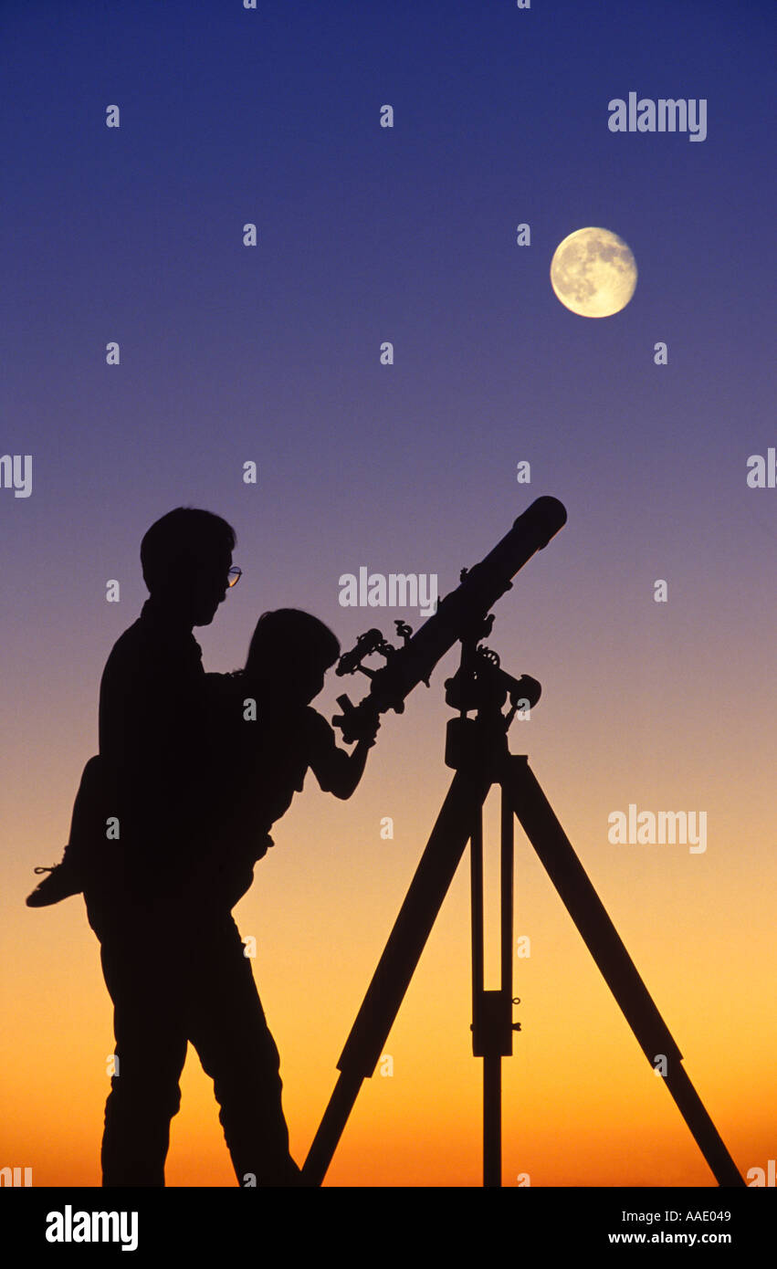 A father holds his child to a telescope aimed at a full moon - Stock Image