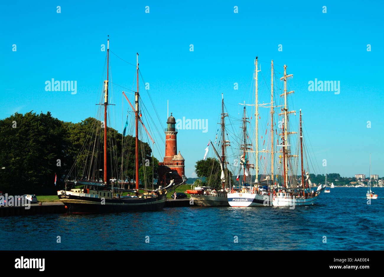 Boats moored near the lighthouse at the entrance to the Kiel Canal Kiel Holtenau Germany - Stock Image