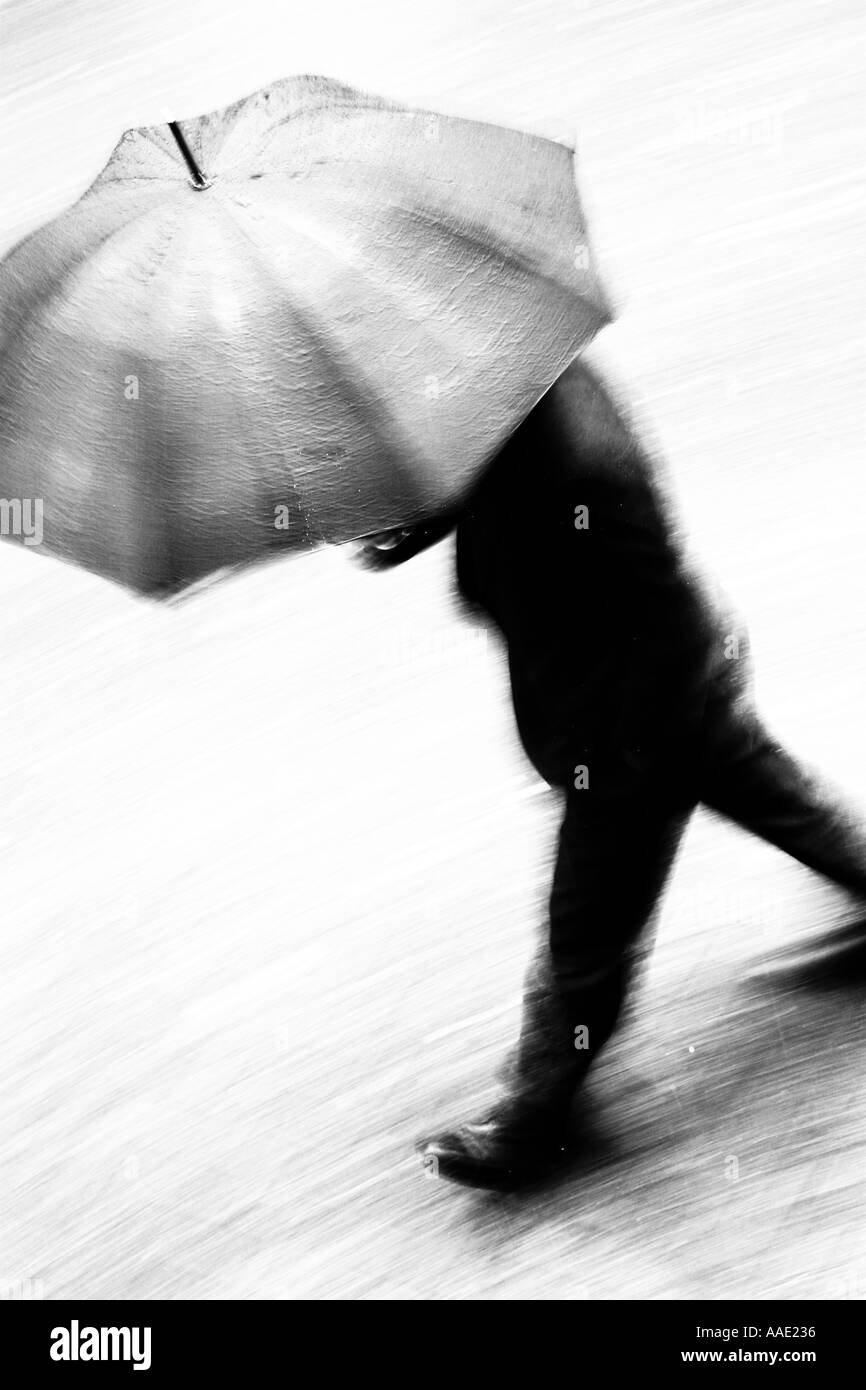 A business man in suit walking at speed under an umbrella in the rain with blurred movement, Chester, Cheshire, UK - Stock Image