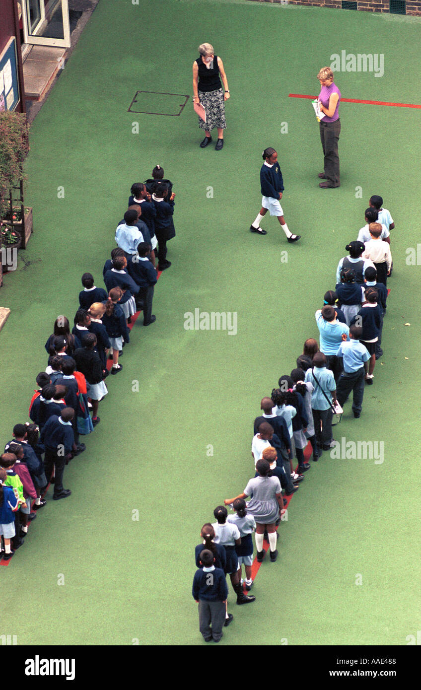 Schoolchildren in line on a school playground London England Britain UK - Stock Image
