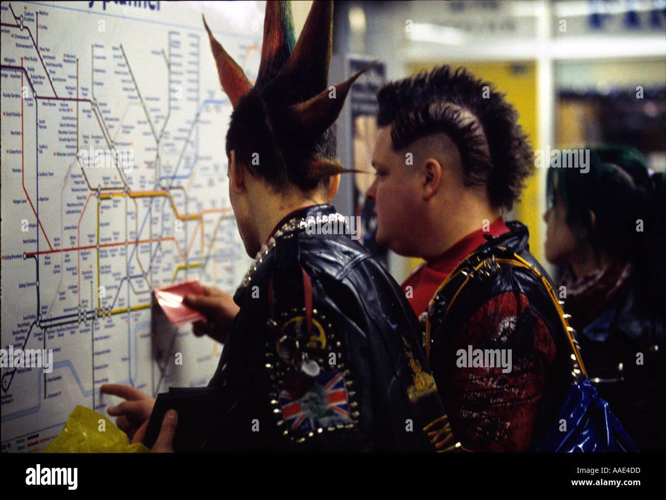 Punks checking tube map in London Underground, England, UK. - Stock Image