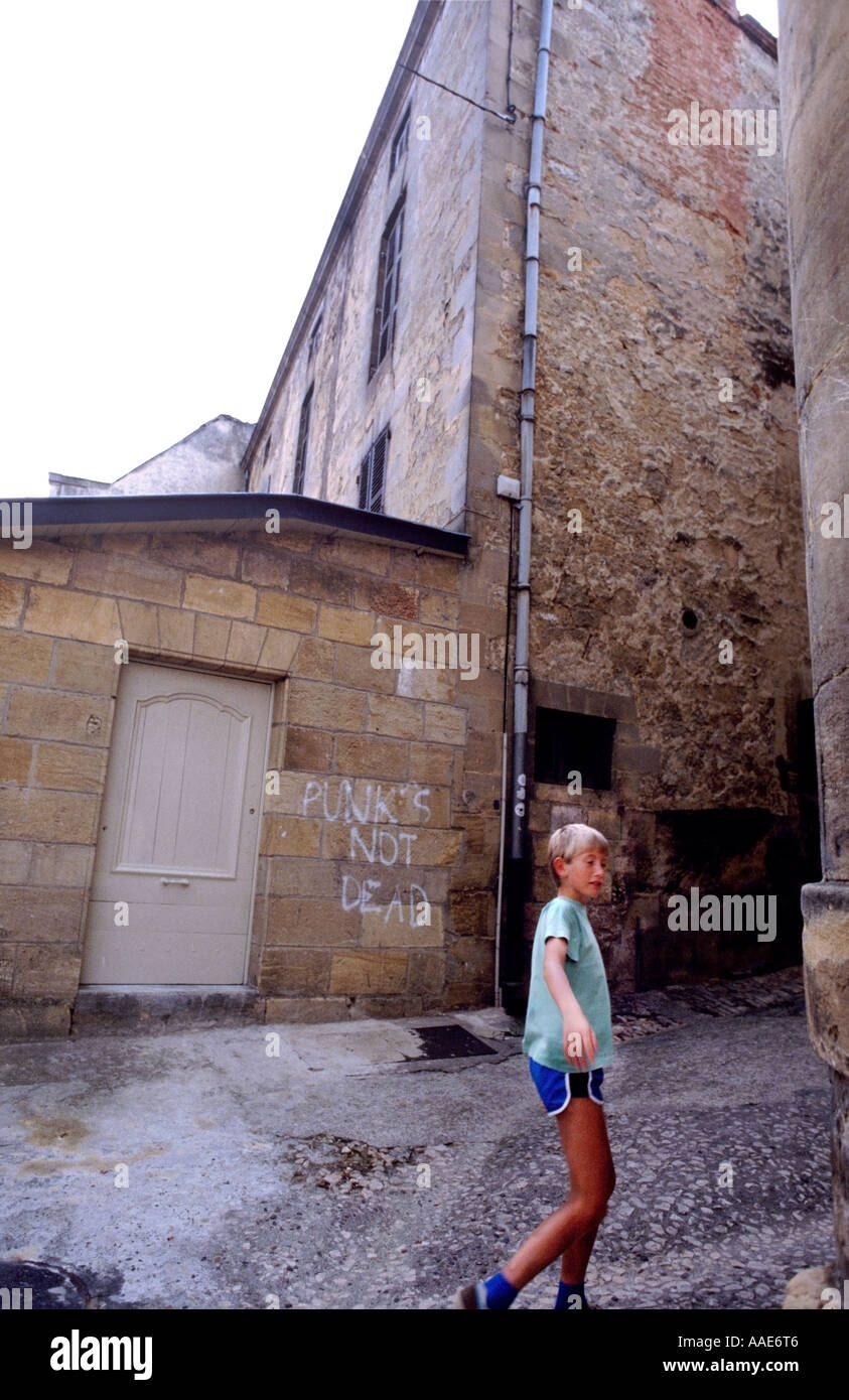 Boy walks past graffitti in French Town - Stock Image