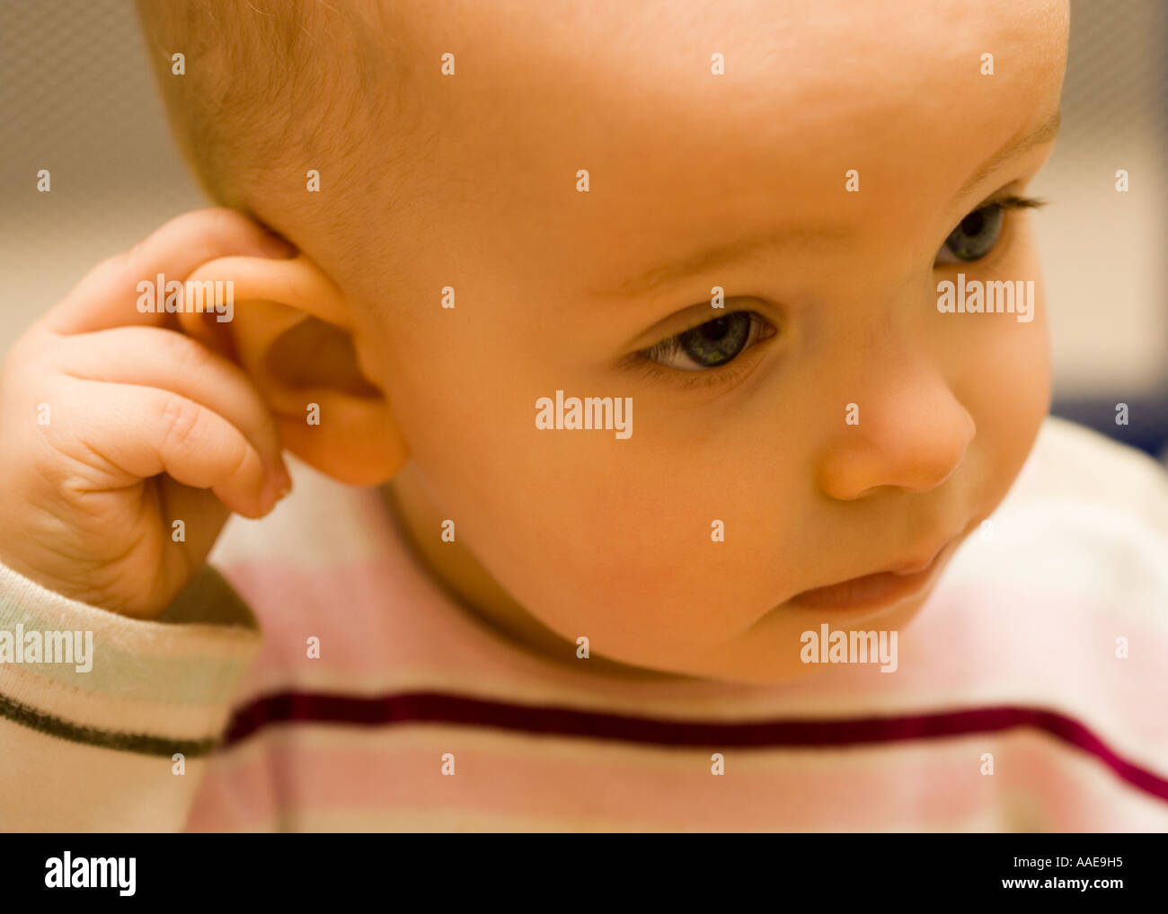 Baby Girl at 10 months holding her ear - very serious - Stock Image