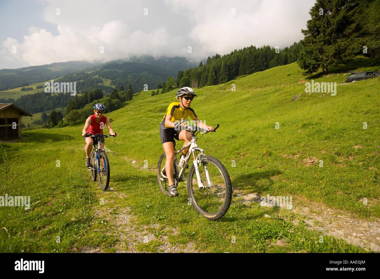 Two women riding mountain bikes Amoseralm Dorfgastein Gastein Valley Salzburg Austria - Stock Image