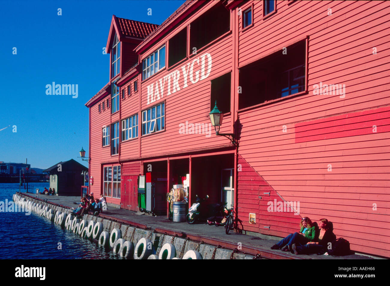 people enjoying the sunshine in Bergen Norway beside a colourful seahouse - Stock Image
