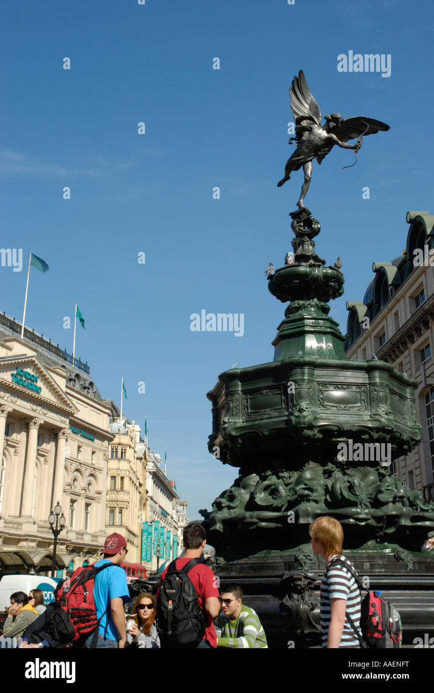 Tourists underneath statue of Eros with the London Trocadero in the distance London England - Stock Image