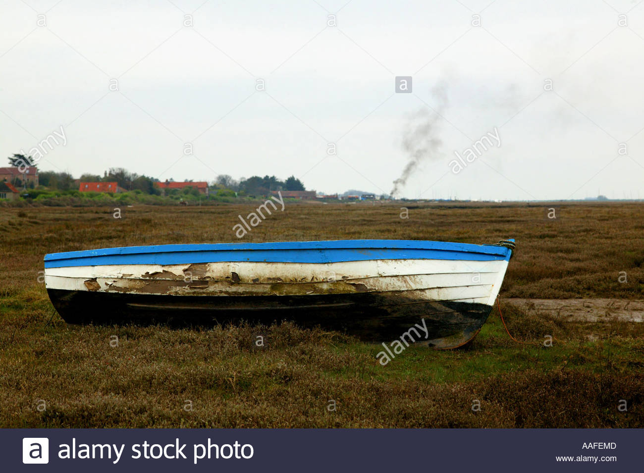Blue and white rowing boat moored at Brancaster-Staithe, North Norfolk, England with smoke in the distance. - Stock Image