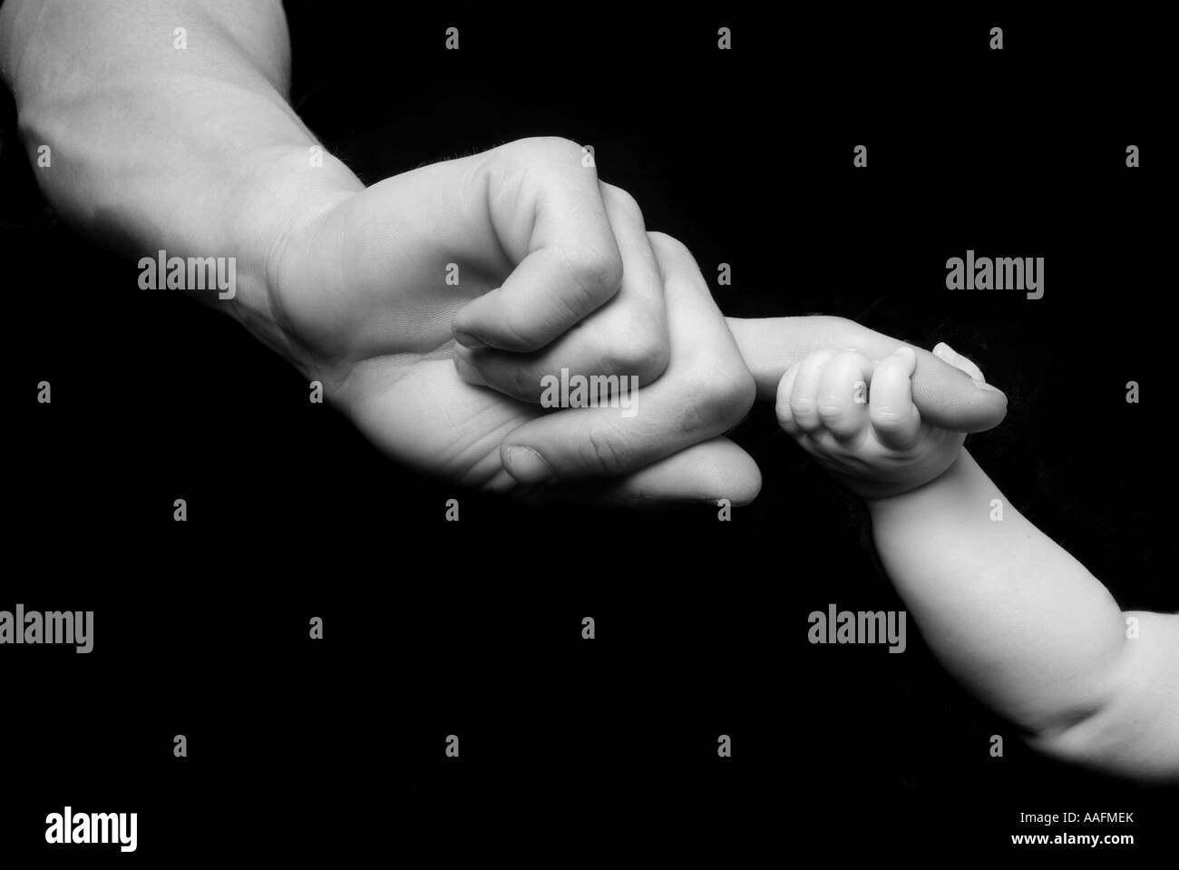 A young baby holding the parents finger.  Shot in black and white and on a black background. - Stock Image