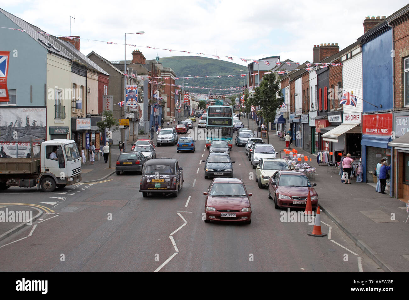 Loyalist Union Jack flags logos murals signs and graffiti with traffic on Shankill Road - Stock Image