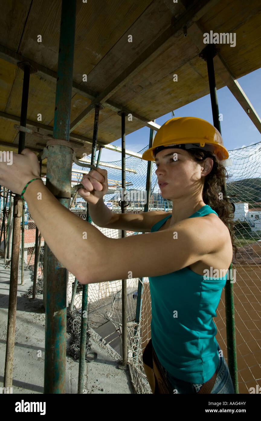 Female construction worker adjusting acro prop - Stock Image