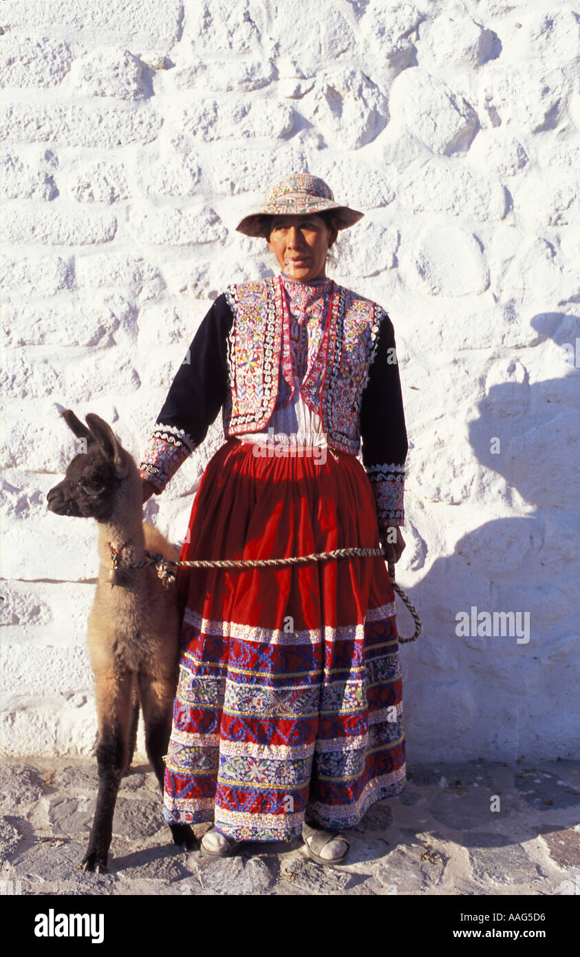 Quechua woman with 12 day old llama in tribal costume at Maca village near Chivay Colca Canyon Peru South America Stock Photo
